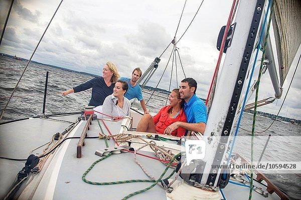 Familie entspannt auf dem Segelboot  schaut lächelnd weg
