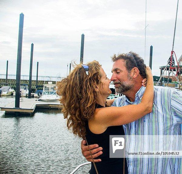Reife Paare im Yachthafen Nase an Nase lächelnd