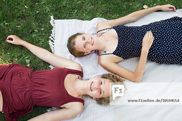 Overhead-Porträt zweier Teenager-Mädchen auf Picknickdecke im Park