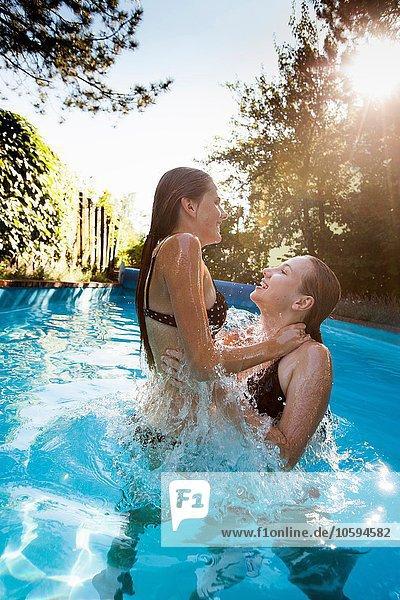 Zwei Teenager-Mädchen beim Springen und Plantschen im Schwimmbad