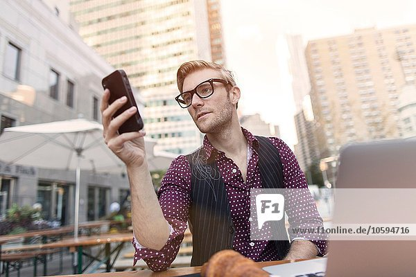 Stressed young businessman reading smartphone at sidewalk cafe  New York  USA