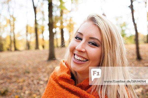 Porträt einer jungen Frau mit langen blonden Haaren in Decke gehüllt im Herbstwald