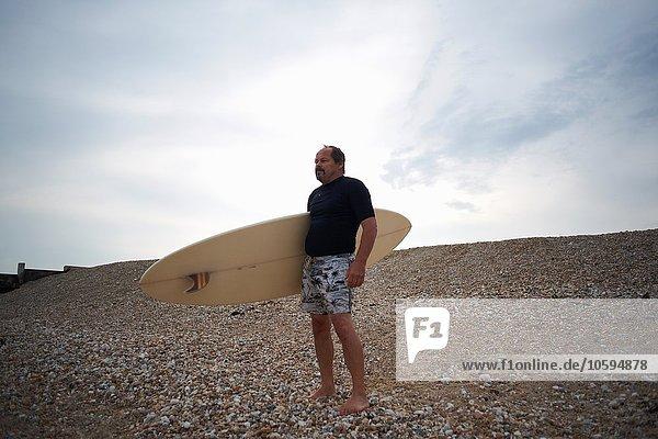 Surfer mit Surfbrett am Strand