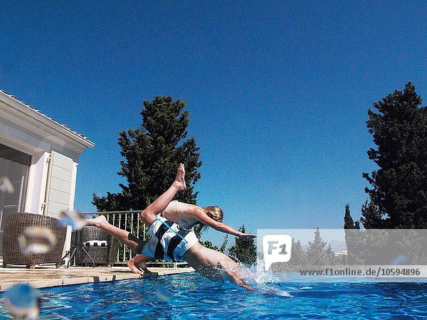 Mädchen und Teenager-Bruder tauchen in die Wohnung Schwimmbad