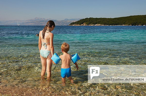 Rear view of girl and boy wearing blue armbands paddling in sea  Corfu  Greece