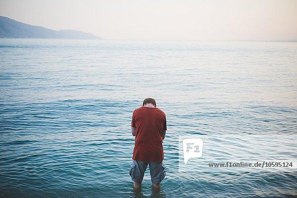 Mann mit Kopf unten stehend im Gardasee  Italien