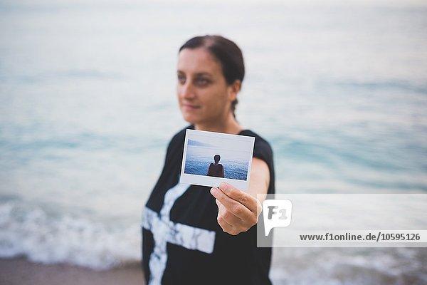 Frau hält ein Foto von sich selbst am Strand hoch.