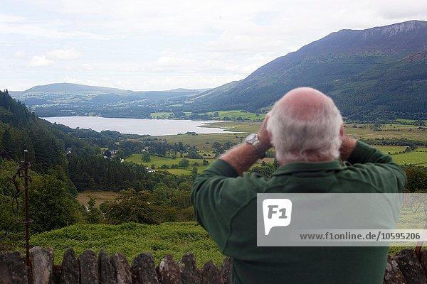Rear view of man birdwatching at viewpoint between Braithwaite Village and Whinlatter  Cumbria  UK