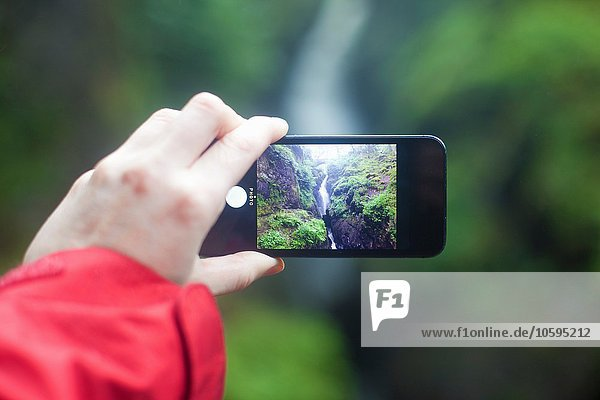 Womans hand holding smartphone  photographing Aira Force waterfall  Penrith  Cumbria  UK