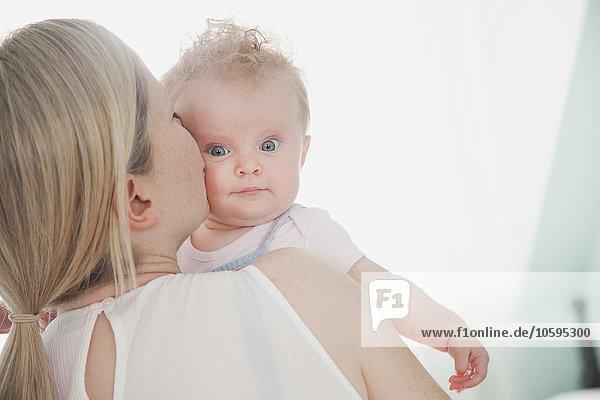 Mutter küsst kleine Tochter