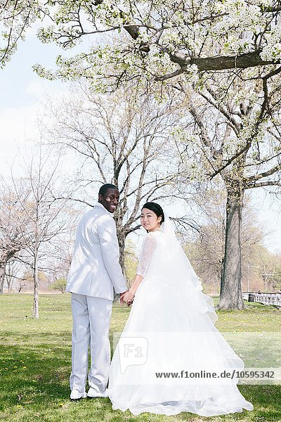 Braut und Bräutigam unter blühendem Baum  Blick über die Schulter auf die Kamera lächelnd