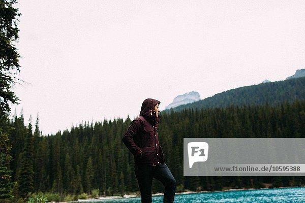 Flachwinkelansicht eines erwachsenen Mannes in wasserdichtem Mantel am Moraine Lake  Hände in Taschen  Banff National Park  Alberta Canada