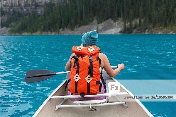 Rückansicht der mittleren erwachsenen Frau mit orangefarbenem Rucksackpaddelboot  Moraine Lake  Banff National Park  Alberta Canada