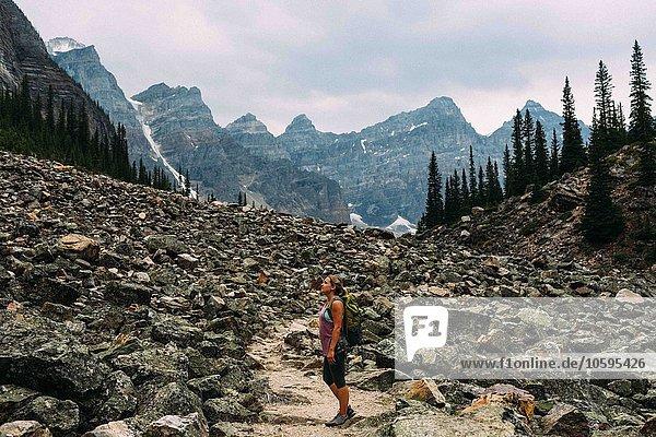 Seitenansicht der mittleren erwachsenen Frau auf einer Felslandschaft unterhalb der Bergkette  Moränensee  Banff Nationalpark  Alberta Canada