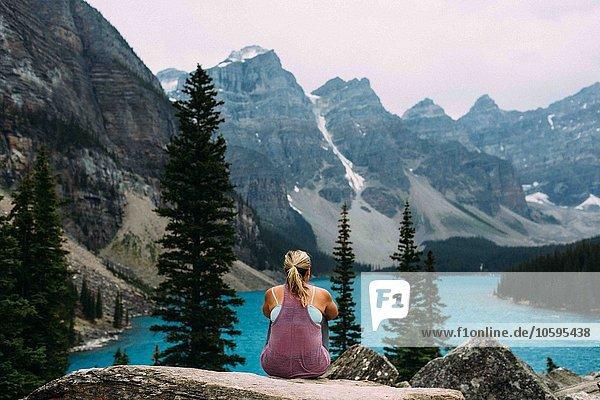 Rückansicht der mittleren erwachsenen Frau am Felsrand mit Blick auf den Moraine Lake  Banff National Park  Alberta Canada