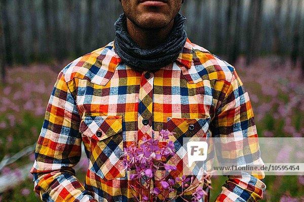 Ausschnitt eines erwachsenen Mannes in kariertem Hemd mit Wildblumen  Moraine Lake  Banff National Park  Alberta Canada