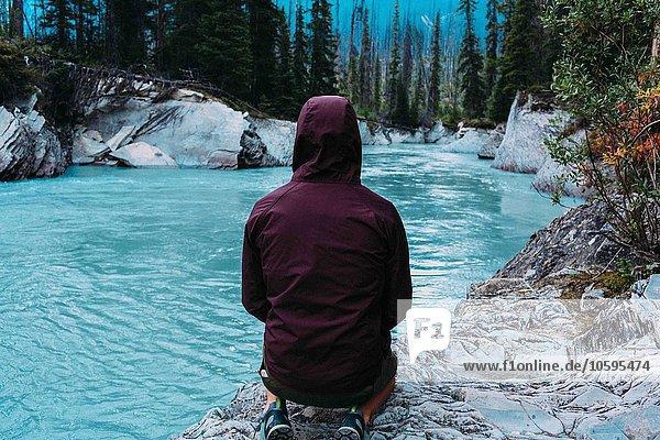 Rückansicht eines erwachsenen Mannes in wasserdichtem Kapuzenmantel am Ufer  Moränensee  Banff National Park  Alberta Canada