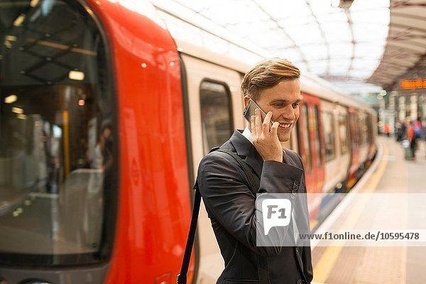 Geschäftsmann mit Telefon am Bahnsteig  U-Bahnhof  London  UK Geschäftsmann mit Telefon am Bahnsteig, U-Bahnhof, London, UK