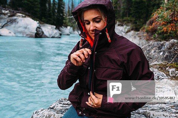 Mittlere erwachsene Frau am Wasser mit wasserdichtem Mantel  Moraine Lake  Banff National Park  Alberta Canada