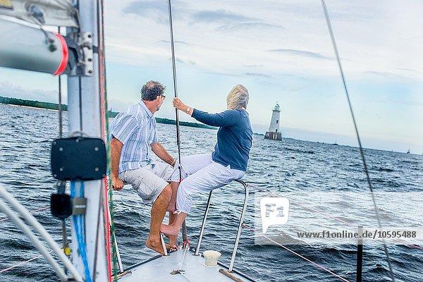 Erwachsenes Paar am Bug eines Segelbootes mit Blick auf den Leuchtturm