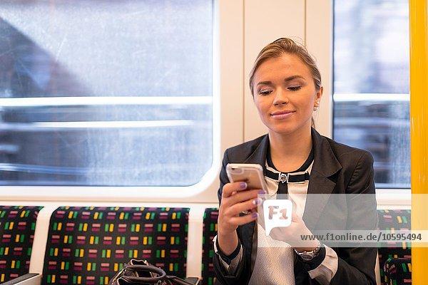 Businesswoman texting on tube  London Underground  UK