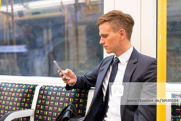 Geschäftsmann texting on tube  London Underground  UK Geschäftsmann texting on tube, London Underground, UK