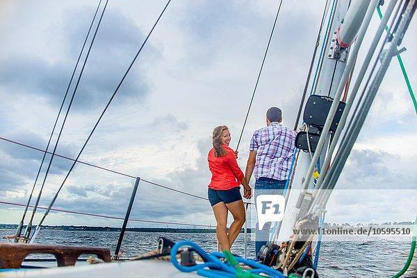 Rückansicht des Paares auf dem Bug des Bootes  über die Schulter schauend  lächelnd auf die Kamera.