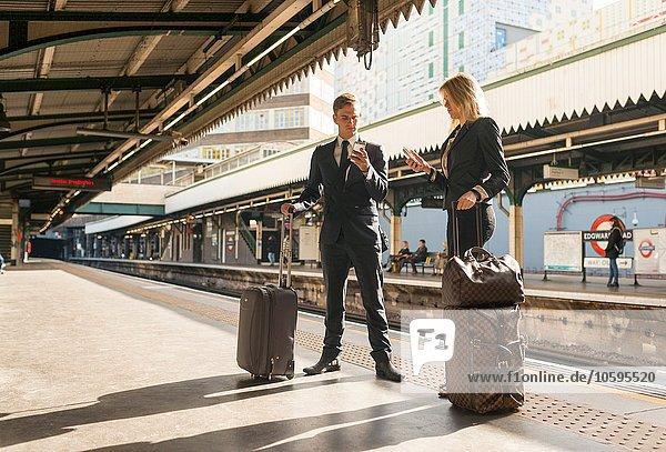 Geschäftsmann und Geschäftsfrau texten auf dem Bahnsteig  U-Bahnhof  London  UK