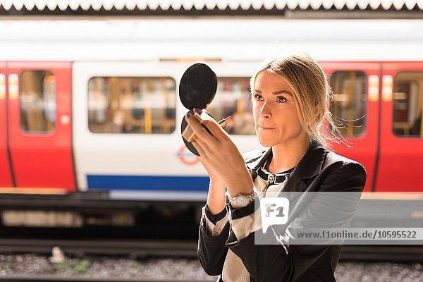 Businesswoman powdering nose  London Underground  UK