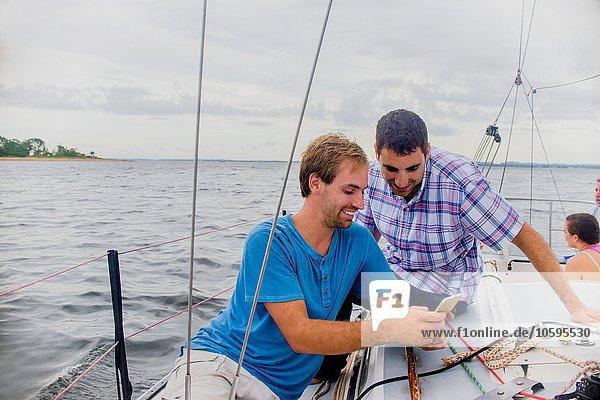 Männer auf dem Segelboot schauen lächelnd auf das Handy