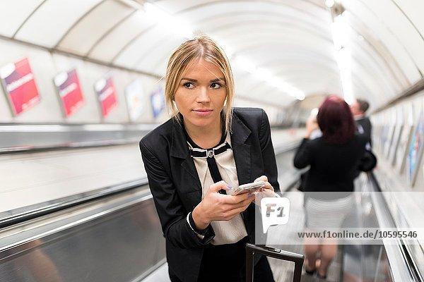 Geschäftsfrau SMS auf Rolltreppe  London Underground  UK Geschäftsfrau SMS auf Rolltreppe, London Underground, UK