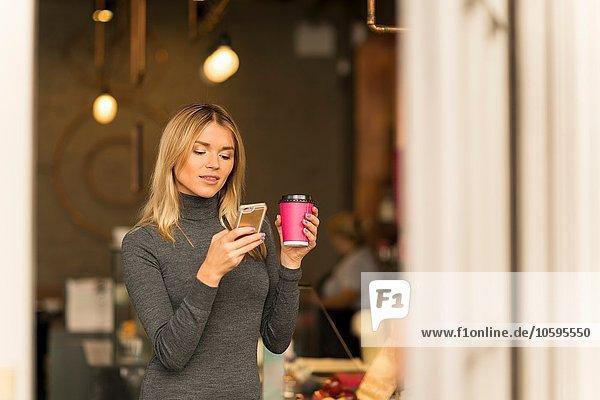 Frau mit Kaffee zum Mitnehmen per Smartphone Frau mit Kaffee zum Mitnehmen per Smartphone