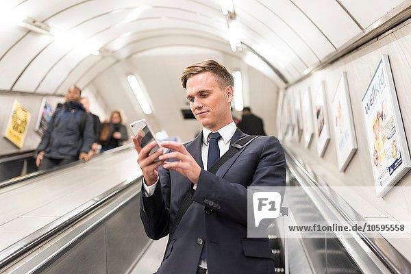 Geschäftsmann SMS auf Rolltreppe  London Underground  UK Geschäftsmann SMS auf Rolltreppe, London Underground, UK
