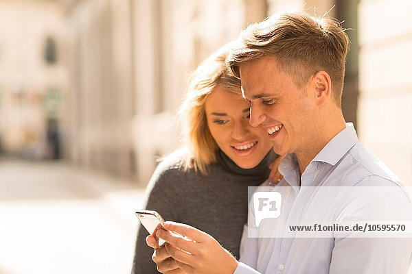 Couple sharing text message in street