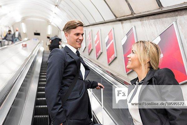 Businessman and businesswoman on escalator  London Underground  UK
