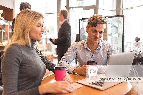 Geschäftsmann und Geschäftsfrau mit Laptop im Café