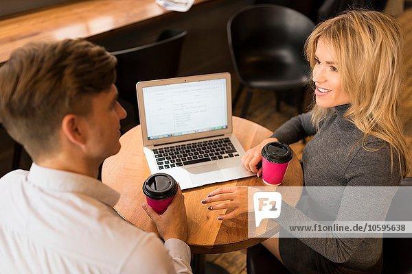 Geschäftsmann und Geschäftsfrau mit Laptop im Café Geschäftsmann und Geschäftsfrau mit Laptop im Café