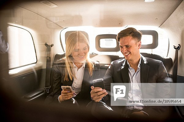 Businessman and businesswoman using smartphone in black cab  London  UK
