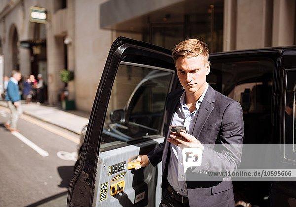 Geschäftsmann mit Smartphone beim Verlassen des schwarzen Taxis  London  UK Geschäftsmann mit Smartphone beim Verlassen des schwarzen Taxis, London, UK