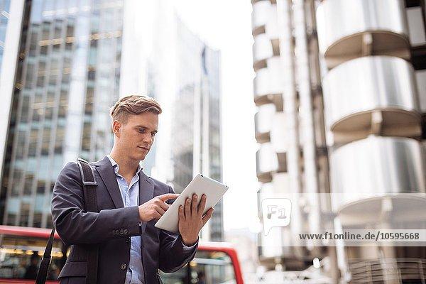 Geschäftsmann mit digitalem Tablett in der Straße  London  UK Geschäftsmann mit digitalem Tablett in der Straße, London, UK