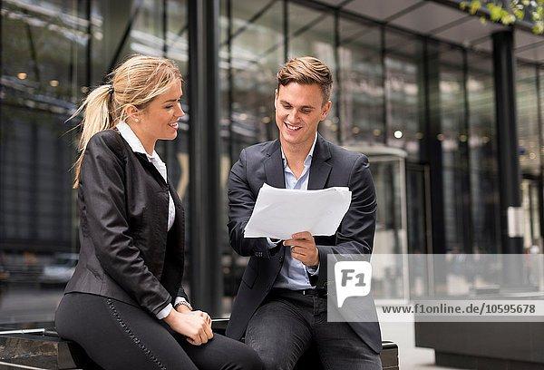 Geschäftsmann und Geschäftsfrau treffen sich vor dem Bürogebäude  London  UK