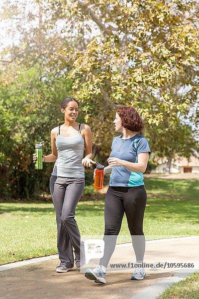Junge Frauen  die in Sportbekleidung mit Wasserflaschen spazieren gehen  reden