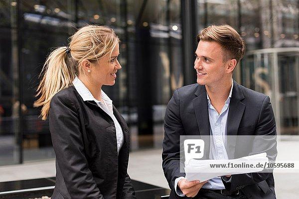 Geschäftsmann und Geschäftsfrau treffen sich vor dem Bürogebäude  London  UK Geschäftsmann und Geschäftsfrau treffen sich vor dem Bürogebäude, London, UK