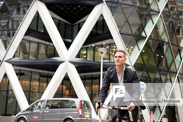 Geschäftsmann auf dem Fahrrad  30 St Mary Axe im Hintergrund  London  UK Geschäftsmann auf dem Fahrrad, 30 St Mary Axe im Hintergrund, London, UK
