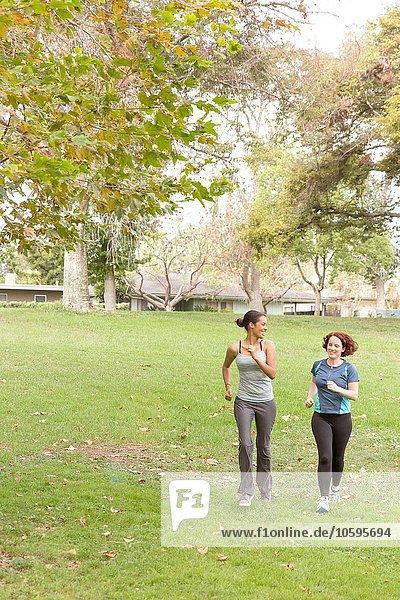 Durchgehende Vorderansicht von Frauen,  die Sportbekleidung auf Rasen tragen.