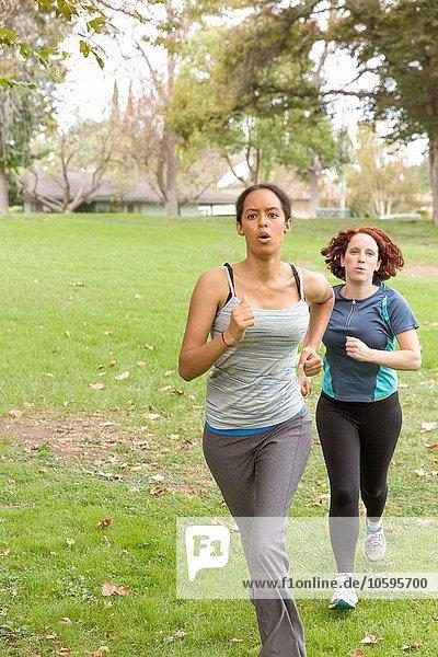 Frontansicht von Frauen  die Sportbekleidung tragen  die auf Rasen laufen.