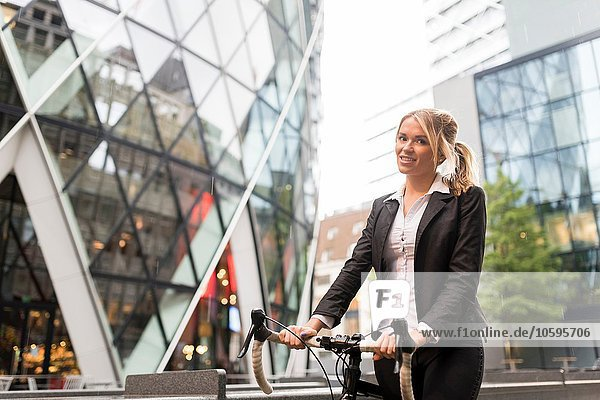 Businesswoman with bike outside 30 St Mary Axe  London  UK