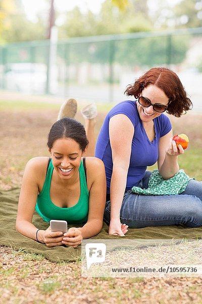 Junge Frauen auf Picknickdecke mit dem Smartphone lächelnd nach unten schauend