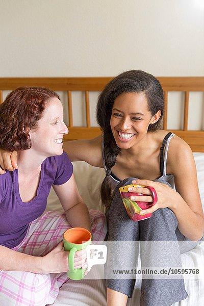 Junge Frauen sitzen auf dem Bett  Arm um Freund  halten Tasse lächelnd