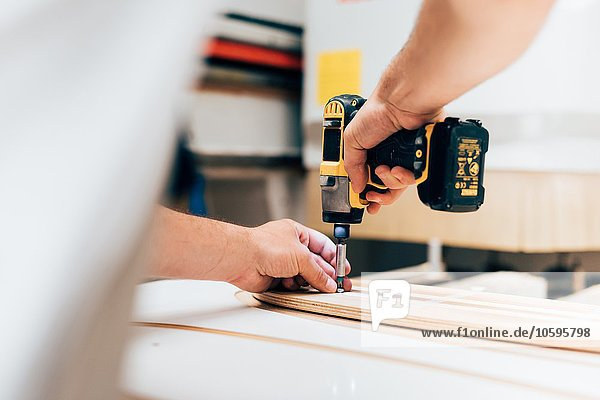 Cropped view of young man in carpentry workshop using cordless screwdriver  screwing into plywood